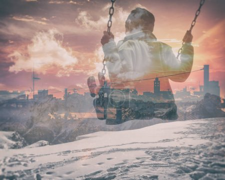 Multiple exposure of kid on swing and city skyline with snowy mountainscape