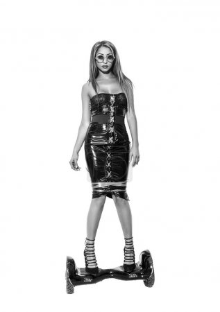 Beautiful woman wearing latex dress and standing on hoverboard, monochrome