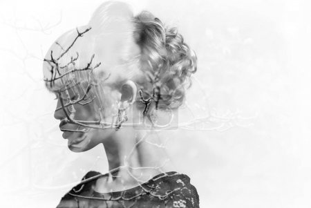Monochrome double exposure of woman with gorgeous hairdo and autumn branches