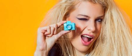 Beautiful girl portrait holding mini toy camera and winking, letterbox