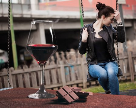 Red wine glass with chocolate and beautiful girl sitting on seesaw