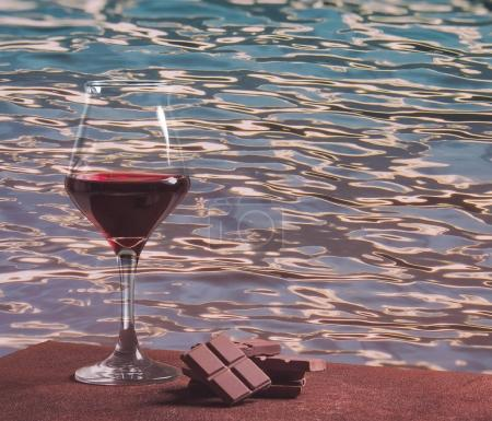 Red wine glass with chocolate and colorful water waves pattern