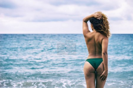 Back portrait of beautiful woman with gorgeous curly hair looking at sea