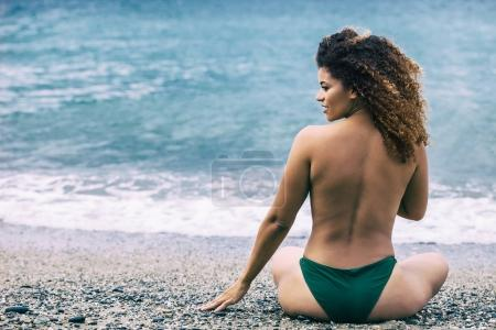 Woman portrait with gorgeous curly hair sitting on beach and looking aside