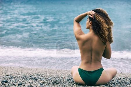 Woman portrait with gorgeous curly hair sitting on beach and looking at sea