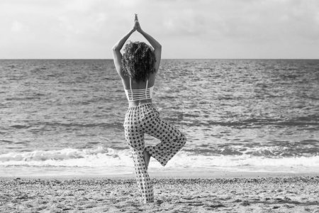 Beautiful woman with curly hair doing yoga on the beach, black and white