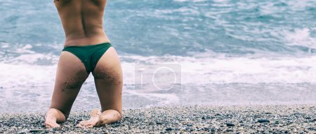 Woman portrait kneeling on beach and looking at sea, letterbox