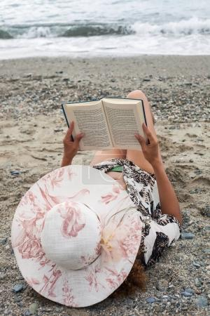 Woman portrait relaxing and reading book on the beach