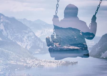 Double exposure of kid on swing and beautiful italian lake glimpse