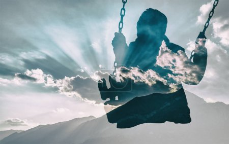Double exposure of kid on swing and gorgeous cloudscape