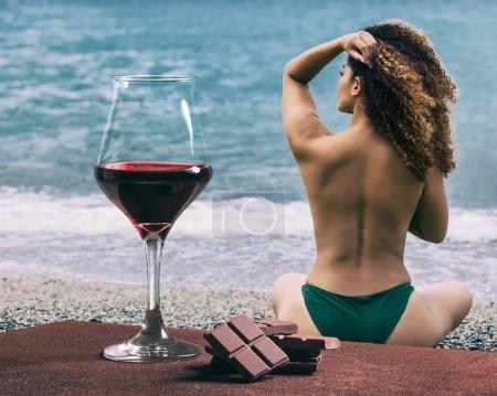 Red wine glass with chocolate and beautiful woman back portrait sitting on the beach