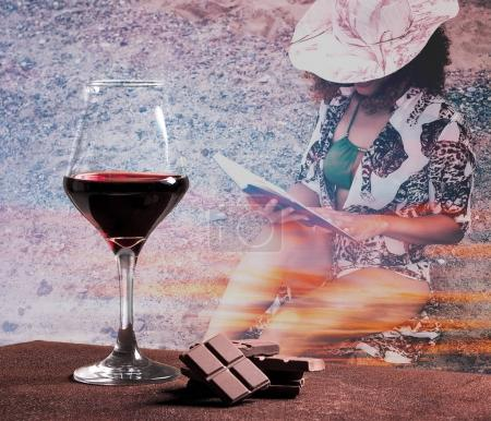 Red wine glass with chocolate and woman portrait reading book with sunset cloudscape
