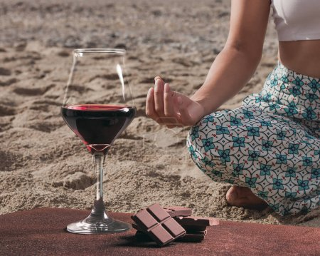 Wine glass with chocolate and woman practicing yoga on the beach