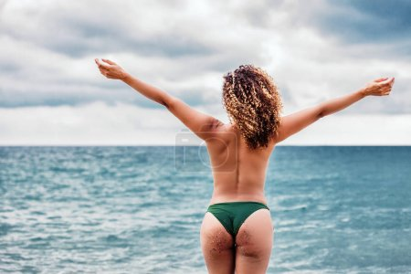 Beautiful woman back portrait feeling free in front of the sea, Summer vacations