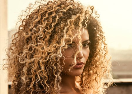 Photo for Beautiful woman with gorgeous curly hair in the sunlight - Royalty Free Image