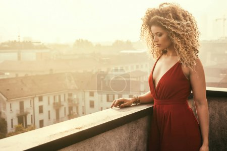 Beautiful woman wearing red elegant dress and being pensive, cityscape