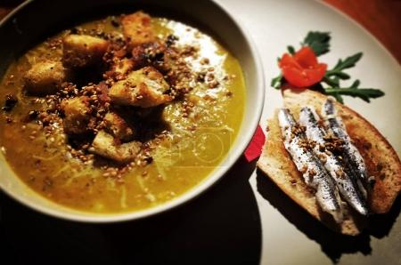 Mixed vegetables pureed soup with seasoned croutons and marinate sardine on bread