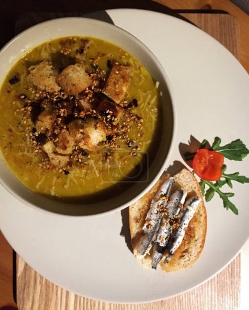 Mixed vegetables pureed soup with seasoned croutons and marinate sardine