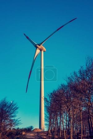 Wind turbine, blue sky and autumn landscape