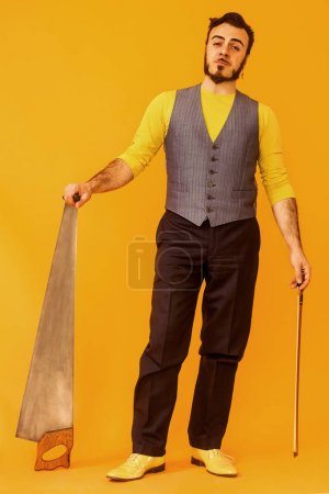 Man portrait posing while holding his musical saw