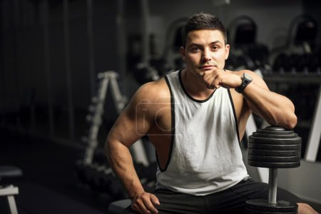 Handsome well built weightlifter sitting thoughtfully