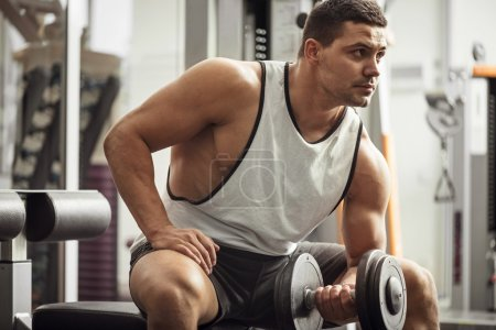 Muscular hard working man holding a dumbbell