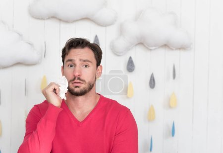 Unhappy ill man standing against cloudy background