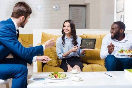 Photo pour Travailler en relation. Positif ravi belle femme d'affaires tenant la tablette et le montrant à ses collègues tout en étant assis à la table et déjeuner ensemble - image libre de droit