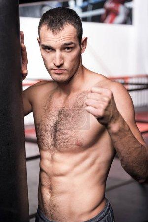 Handsome man standing near punching bag