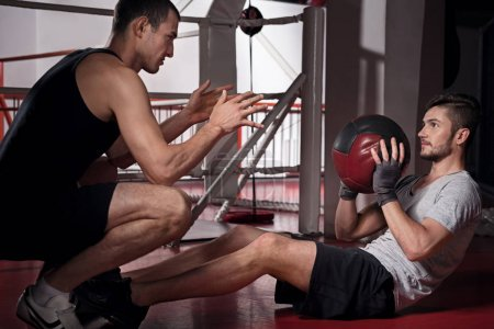 Young man training abdomen with trainer