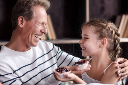 Little girl holding cupcakes with her grandfather