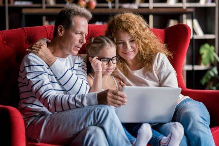 Girl sitting in front of the laptop with her grandparents
