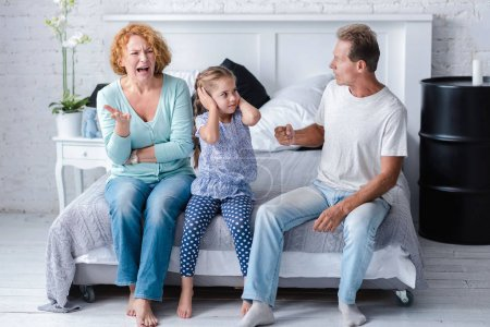 Irritated aged couple quarreling in front of their granddaughter