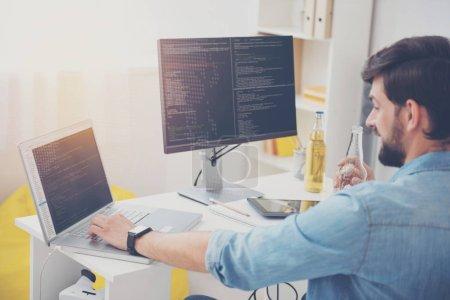 Photo pour Amoureux de la technologie. Jeune programmeur concentré beau codage à l'aide d'un ordinateur portable et un ordinateur tout en travaillant dans un bureau. - image libre de droit