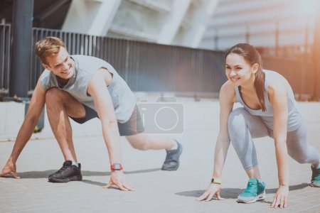 Athletic couple in sprint start position preparing for a run.
