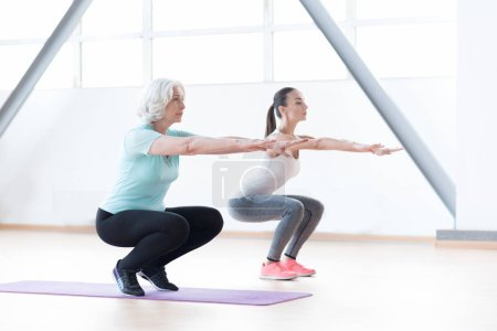 Active well built women squatting