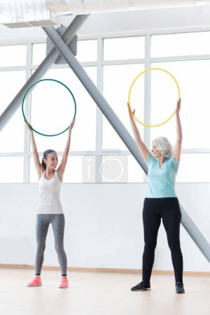 Good looking sporty women holding hula hoops