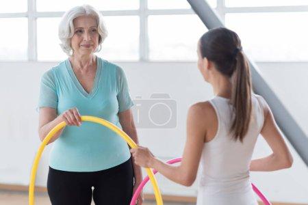 Joyful pleasant women holding a yellow hula hoop