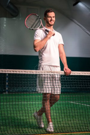 Professional delighted tennis player holding racket