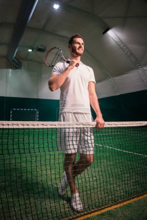 Cheerful professional tennis player training in indoor court