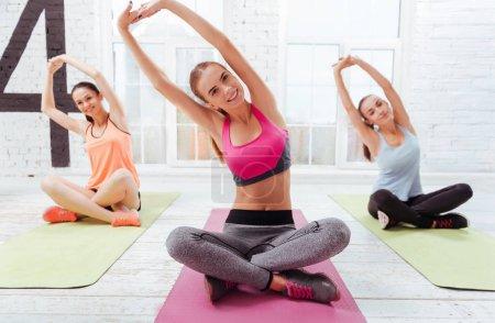 Photo pour Faisons-le. Trois jeunes belles filles ayant yoga du matin et faire des exercices tout en passant du temps dans une salle de gym . - image libre de droit
