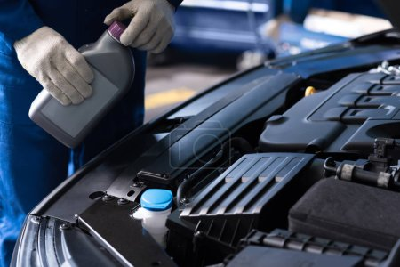 Photo for Make it drive. Close up of bottle with oil in hands of professioanl mechanic holdign it while going to change the liquid in the car - Royalty Free Image