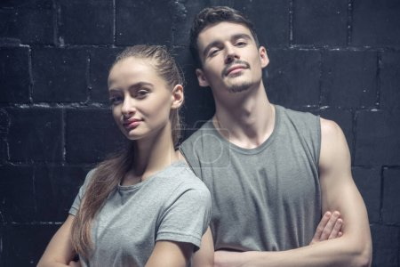 Delighted dancers standing near the black wall with crossed arms