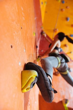 Athletic woman training hard in climbing gym