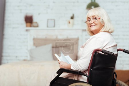 Positive elderly disabled woman resting at home