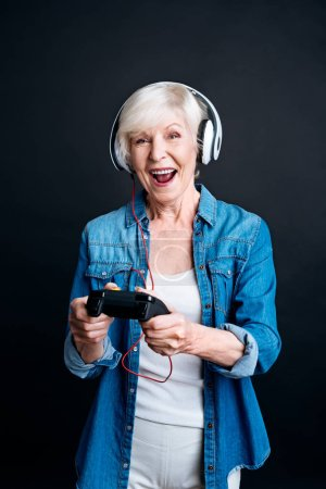 Jubilated senior woman playing video games