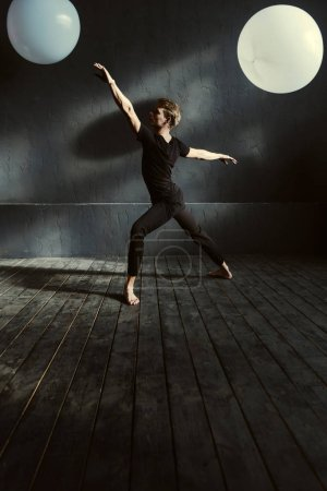 Graceful ballet dancer performing in the decorated studio