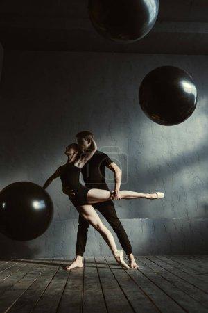 Proficient ballet dancers performing together in the studio