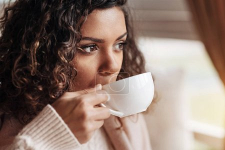 Photo for Enjoying the delicious cup of tea. Charming positive delighted African American woman sitting in the cafe and being covered with a blanket while drinking the cup of tea - Royalty Free Image