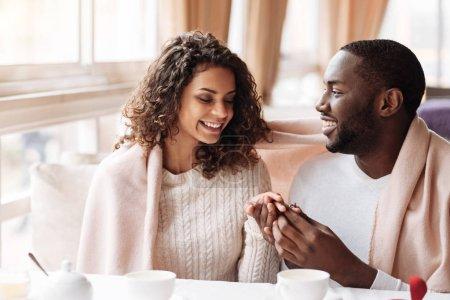 Photo pour La femme la plus heureuse du monde. Souriant heureux couple afro-américain positif assis dans le café et être couvert d'une couverture tout en s'engageant et en exprimant le bonheur - image libre de droit